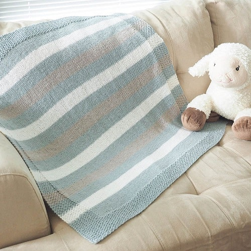Easy Striped Baby Blanket - These knitting patterns for baby blankets are easy and adorable you might find yourself making more than just one! #knittingpatterns #babyblanketknittingpatterns #babyblankets