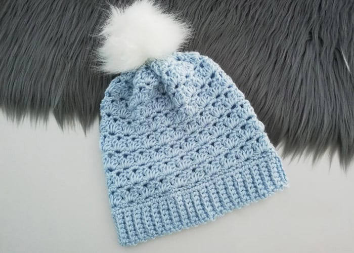 Girls Winter Pompom Hat - These 26 crochet winter hat patterns are perfect to create a winter hat accessory that you love and can rely on. #crochetwinterhat #crochetpatterns #crochethatpatterns